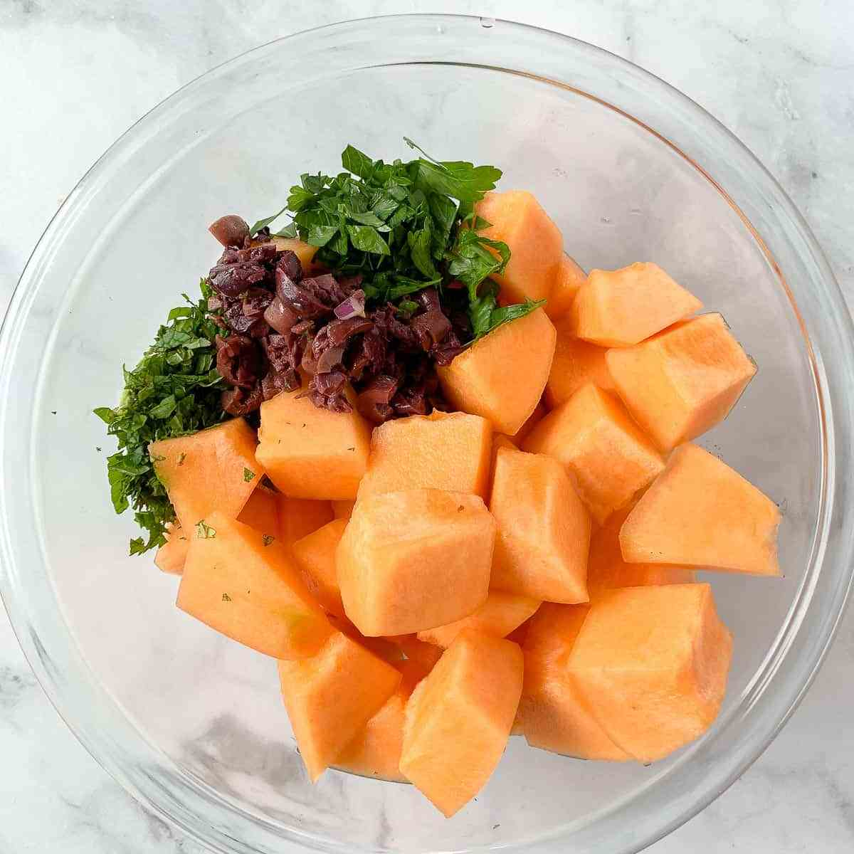 add cantaloupe, herbs and olives to a bowl