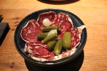 Bowl of French sausage with gherkins