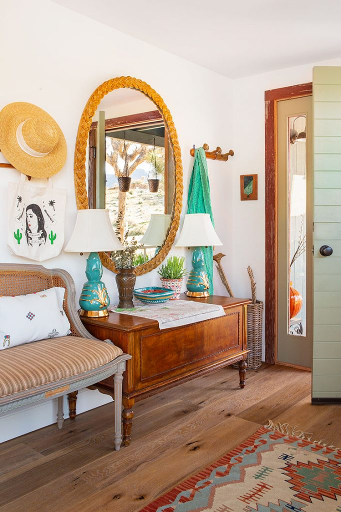 An entryway with blue lamps, an oval mirror, and other reclaimed pieces.