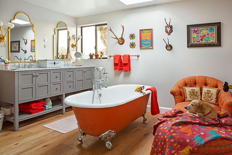 A vintage-inspired claw bathtub tinted a bright orange hue.