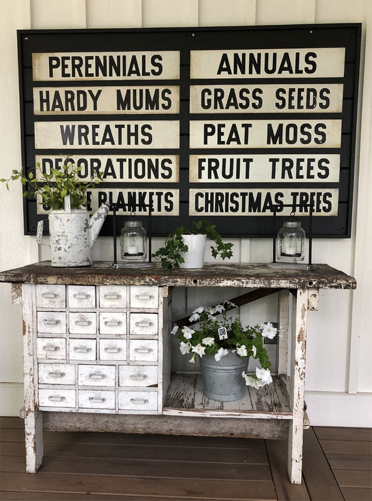 A vintage potter's cabinet with an array of farmhouse foliage and an antique metal signboard overhead as a part of the day in the life narrative.