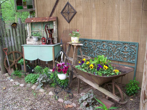 Julie is the queen of the garden vignette. Notice how she layers the furniture, plaques and objects together.