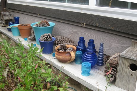 Cobalt vases and Bauer pots made rustic with the contrasting texture of pinecones