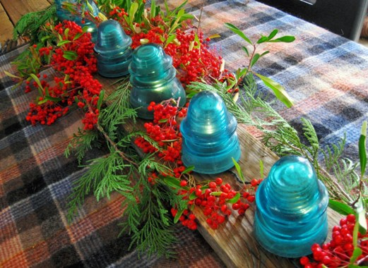 After noticing my pyracantha bush loaded with Winter berries, I set a new table using my aqua glass insulators, cedar branches and the small branches of berries. First I lay down a small plaid blanket and placed an old barn board down the middle as a base. From Jeanne Sammons' idea, I used a battery powered 15 light string and poked every other one under the insulators…..filled in with the branches!