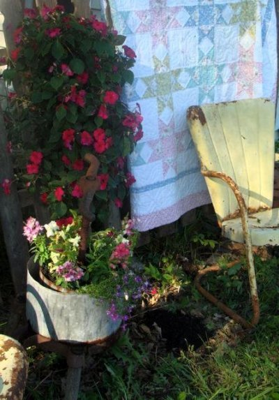 Someone in Rebecca Spencer's garden has hung a quilt for airing,..with an old motel chair