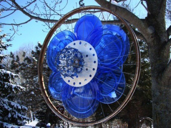 A couple of years ago I started collecting bicycle rims and decided to make a rotating sculpture for year round interest in my yard. Each side is different. The blue disks are glass plates. The center of the 'flower' on the other side is a chimney cleaning brush.