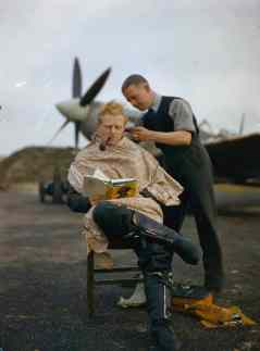 An RAF pilot getting a haircut while reading a book between mission