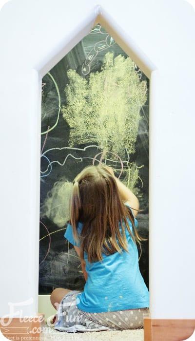 girl drawing on chalkboard wall