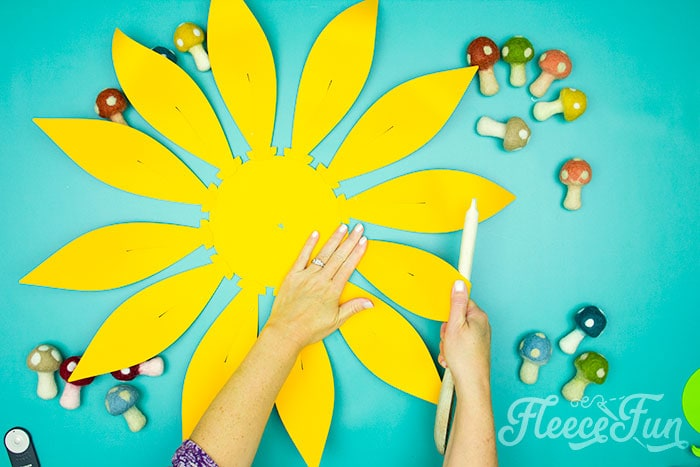 Using spoon to curve petals. This Giant Paper Sunflower DIY (FREE SVG files) is perfect for fall! Make a Giant flower wall or use it to decorate your space! So many possibilities!