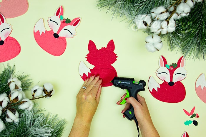 Gluing the tail on. This adorable Felt Fox Ornament DIY (Free Pattern) is a fun addition to your Christmas tree Ornaments! Curled up in it's tail with a bit of holly on it's head this fox is the embodiment of merriment. Use for tree decorations or as a fun addition to a wrapped gift. Also makes a wonderful hostess gift or prize at a holiday party. Perfect handmade ornament to make.
