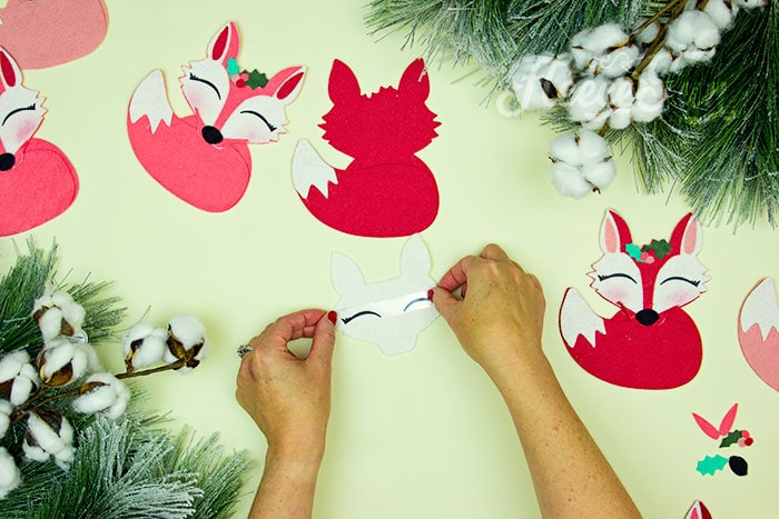 Adding the eyes to the face. This adorable Felt Fox Ornament DIY (Free Pattern) is a fun addition to your Christmas tree Ornaments! Curled up in it's tail with a bit of holly on it's head this fox is the embodiment of merriment. Use for tree decorations or as a fun addition to a wrapped gift. Also makes a wonderful hostess gift or prize at a holiday party. Perfect handmade ornament to make.