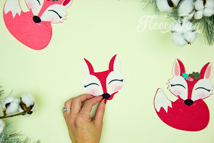 Adding the nose. This adorable Felt Fox Ornament DIY (Free Pattern) is a fun addition to your Christmas tree Ornaments! Curled up in it's tail with a bit of holly on it's head this fox is the embodiment of merriment. Use for tree decorations or as a fun addition to a wrapped gift. Also makes a wonderful hostess gift or prize at a holiday party. Perfect handmade ornament to make.