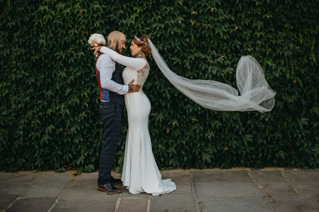 tattooed bride and groom wearing white wedding dress and veil in wind