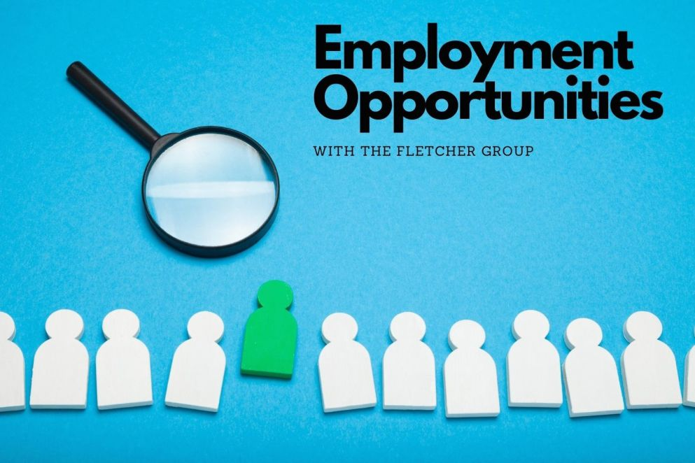 Magnifying glass being used to examine paper cutouts representing job seekers. An image.