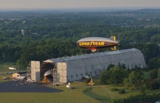 Goodyear airship flying over hangar