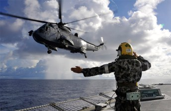The flight deck marshaller, Leading Seaman Andrew Gilmour, signals the Canadian Sea King helicopter to transit across HMAS Toowoomba's flight deck to exit, International Waters, Middle East Area of Operations