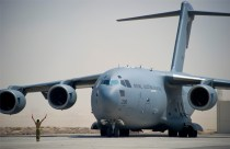 A member of the Royal Australian Air Force (RAAF) marshals a RAAF C-17 Globemaster following the aircraft's arrival in the Middle East