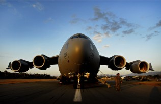 As the sun sets, a Royal Australian Air Force C-17 Globemaster sits on the tarmac after arriving at Dili International Airport, in East Timor