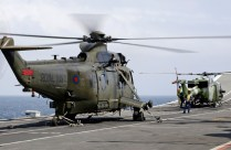 A Sea King helicopter conducts a ground run, after having an engine replaced, on the flight deck of HMS Illustrious in the Middle East Area of Operations