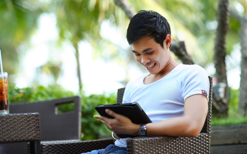 man looking at his tablet and smiling