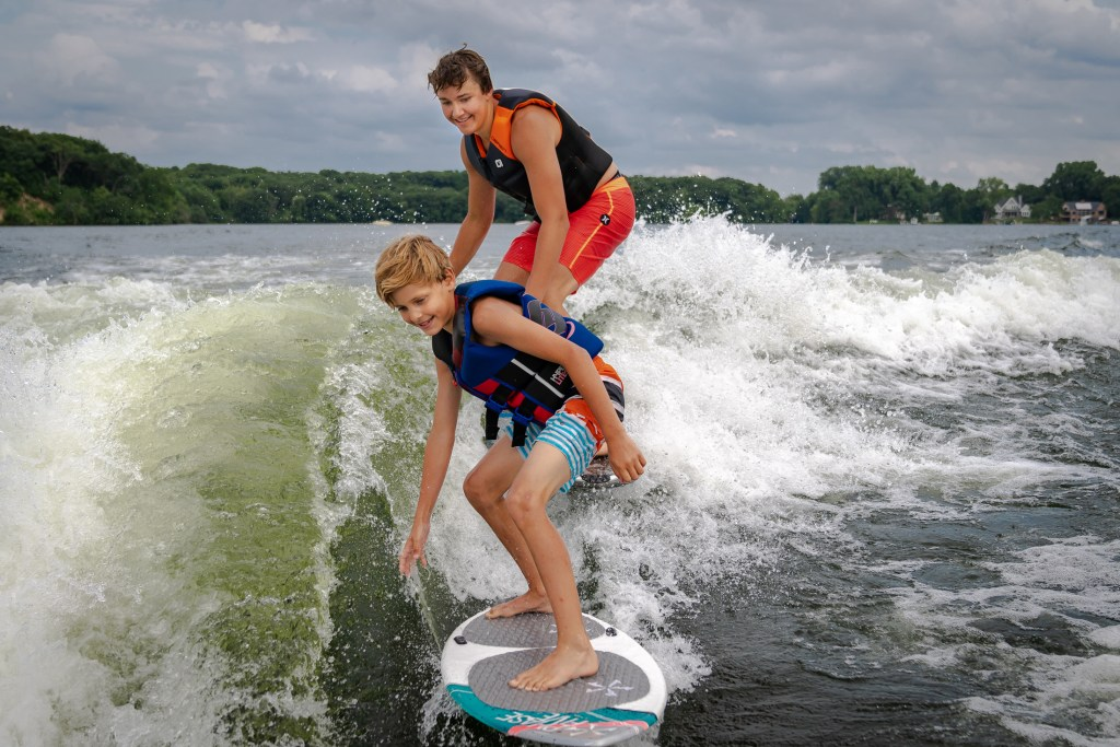 Kids surfing behind the innovative Varatti hull design.