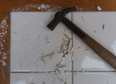 Upcycling a tiled table - removing the old tiles, breaking the old tiles with a hammer