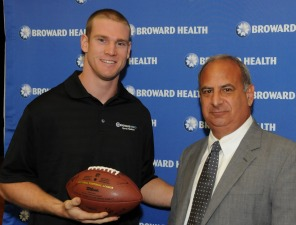 Ryan Tannehill accepts a football signed by all Broward Health orthopedic surgeons from Broward Health President/CEO Frank Nask Photo: Downtown Photo/Ryan Pinder