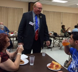 Candidate Perman hovers over Democratic pizza eaters  Photo: Buddy Nevins