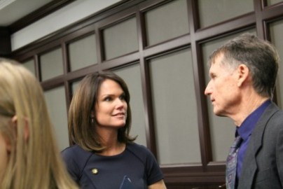 Brunette woman in dark blue top looks at gray-haired man in gray suit, purple shirt.
