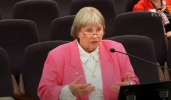 A gray-haired woman wearing glasses in a pink jacket standing at a podium.
