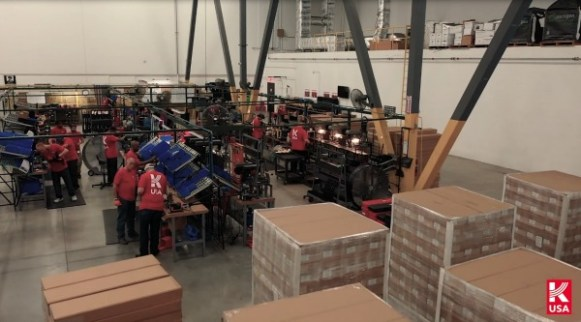 worker wearing red Kalashnikov T-shirts making guns while brown boxes with guns and parts stand nearby