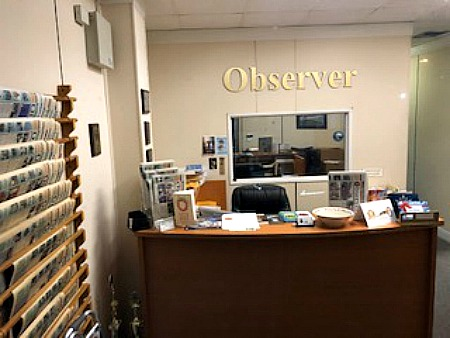 "cluttered desk, black chair in front of a wall with ""Observer"" sign"