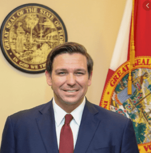 headshot of gov. ron desantis standing in front of the state flag and state seal