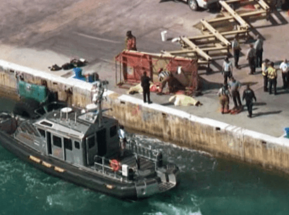 A tugboat waits nearby as authorities examine a toppled scissor left at Port Everglades.