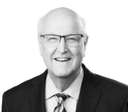 black and white head shot of a white man wearing glasses and dressed in a dark suit and tie.