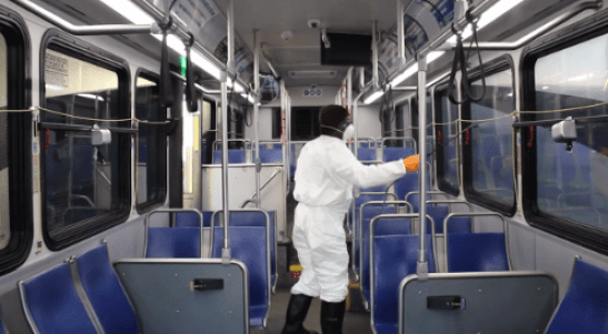 A county employee dressed in protective clothing sprays the inside of a bus to kill the COVID-19 virus.
