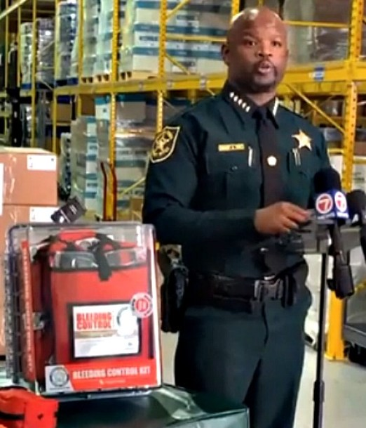 wearing a green uniform, broward sheriff gregory tony speaks with reporters last September. Red bleeding control kits are next to him on a table