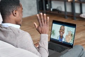 Male black patient talking on conference video call to female african doctor. Virtual therapist consulting young man during online appointment on laptop at home. Telemedicine chat, telehealth meeting