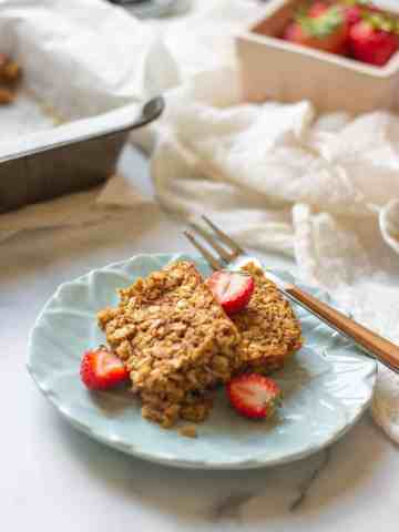 two squares of baked oats with cut up strawberries and on a blue plate