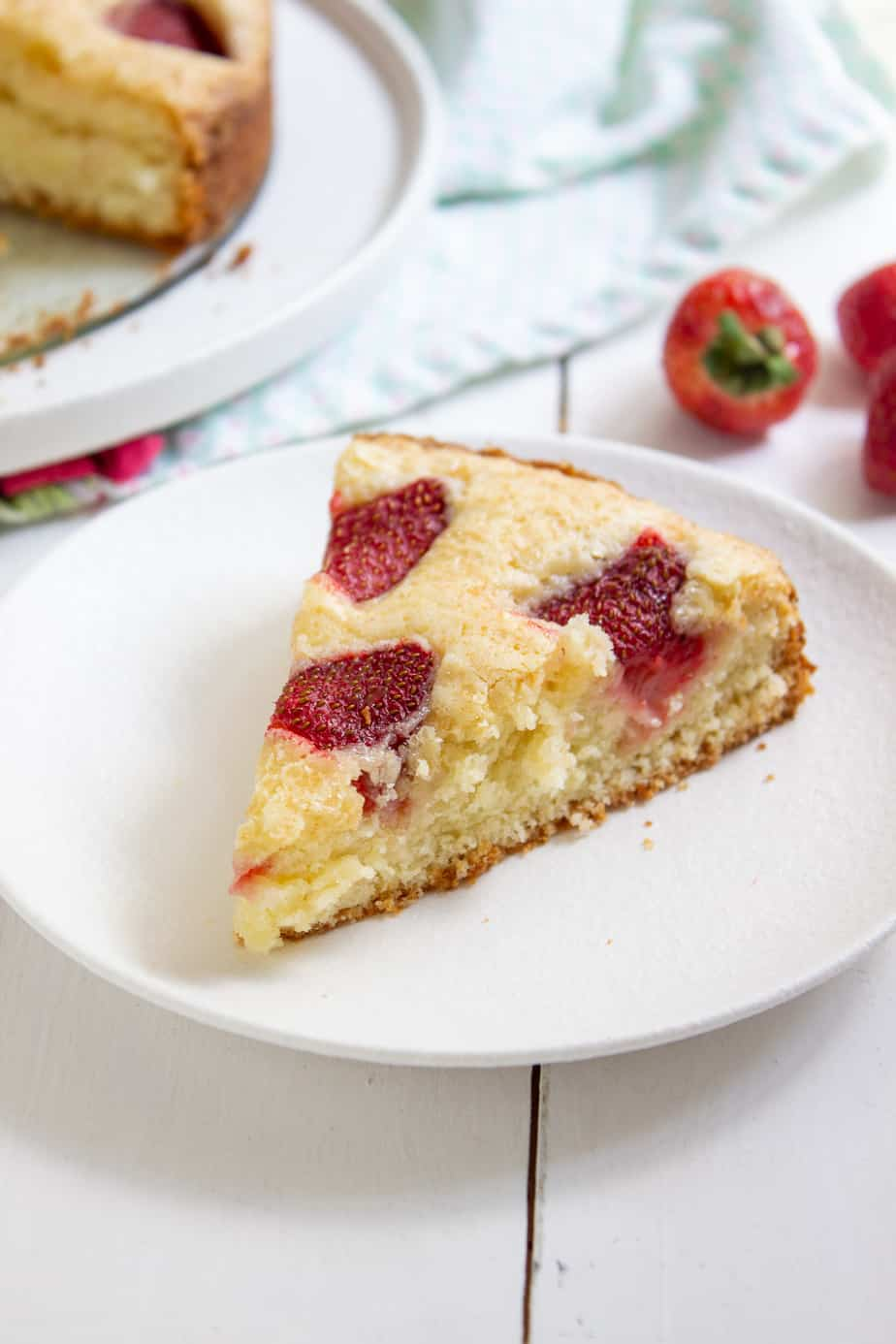 a piece of strawberry cake with a strawberry in the background