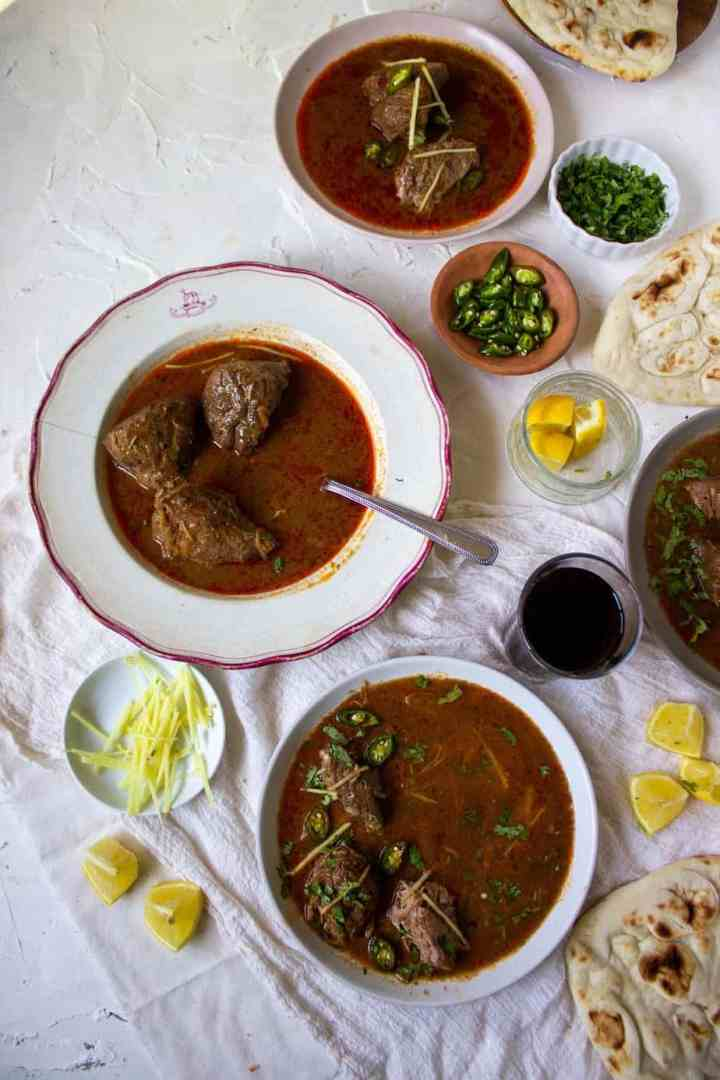 three dishes with nihari in them and little bowls of garnishes and some naan