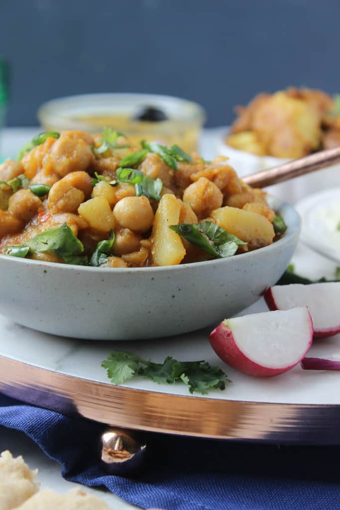 A bowl of aloo chana, two pieces of radish