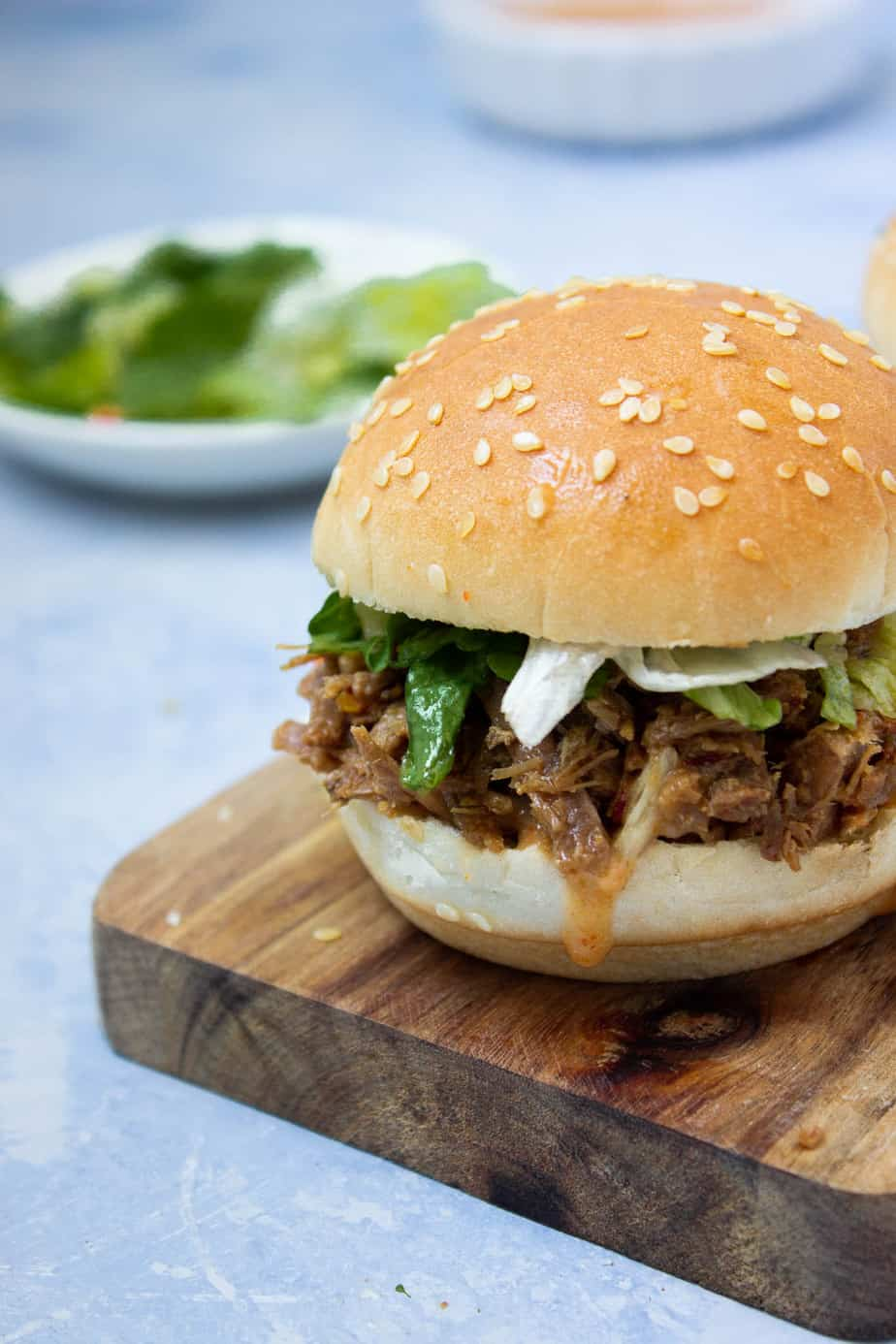 most of a pulled beef slider with lettuce, sauce and some extra greens in the background