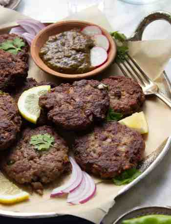 Kachay Qeemay Kay Kabab on a silver platter with parchment paper, chutney and garnishes
