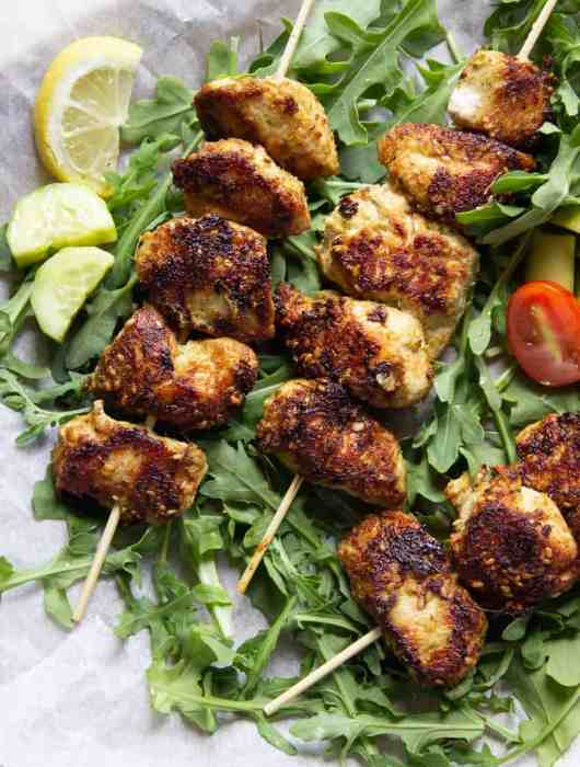 Three Sesame Ginger Chicken skewers on a bed of arugula
