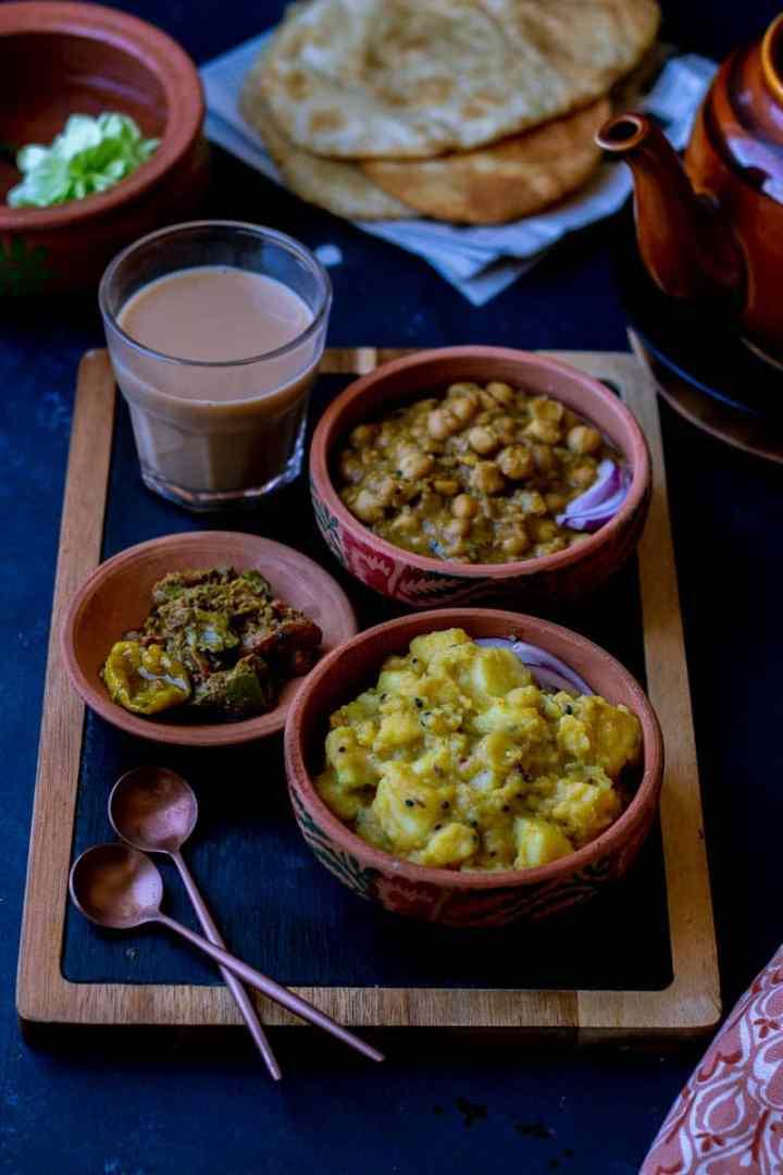 A nashta spread with Poori Aloo, Puri Chole, Achar, Chai and two spoons