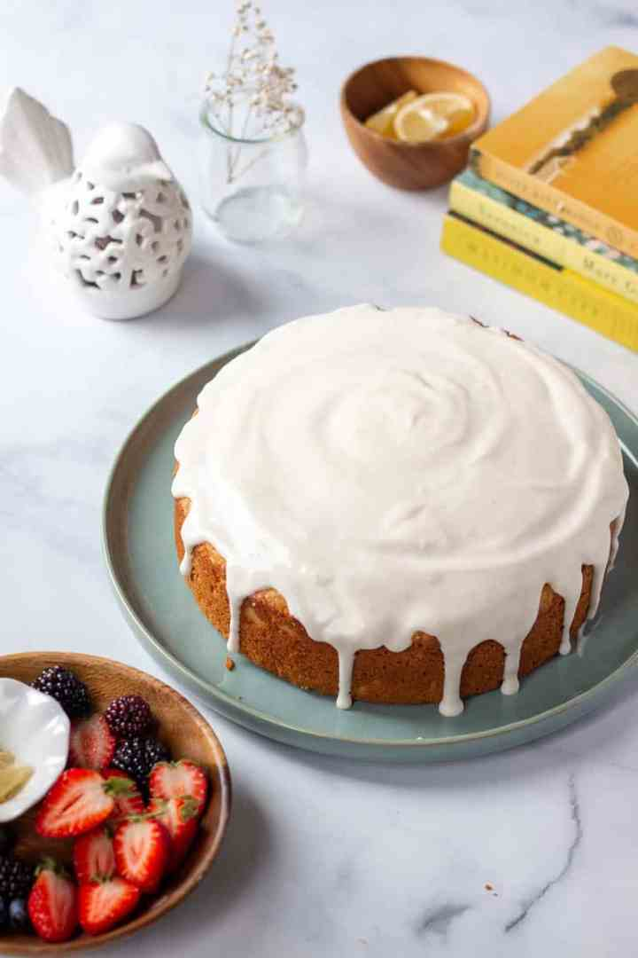 A lemon cake with cream cheese glaze and some yellow and white decorative elements in the back ground