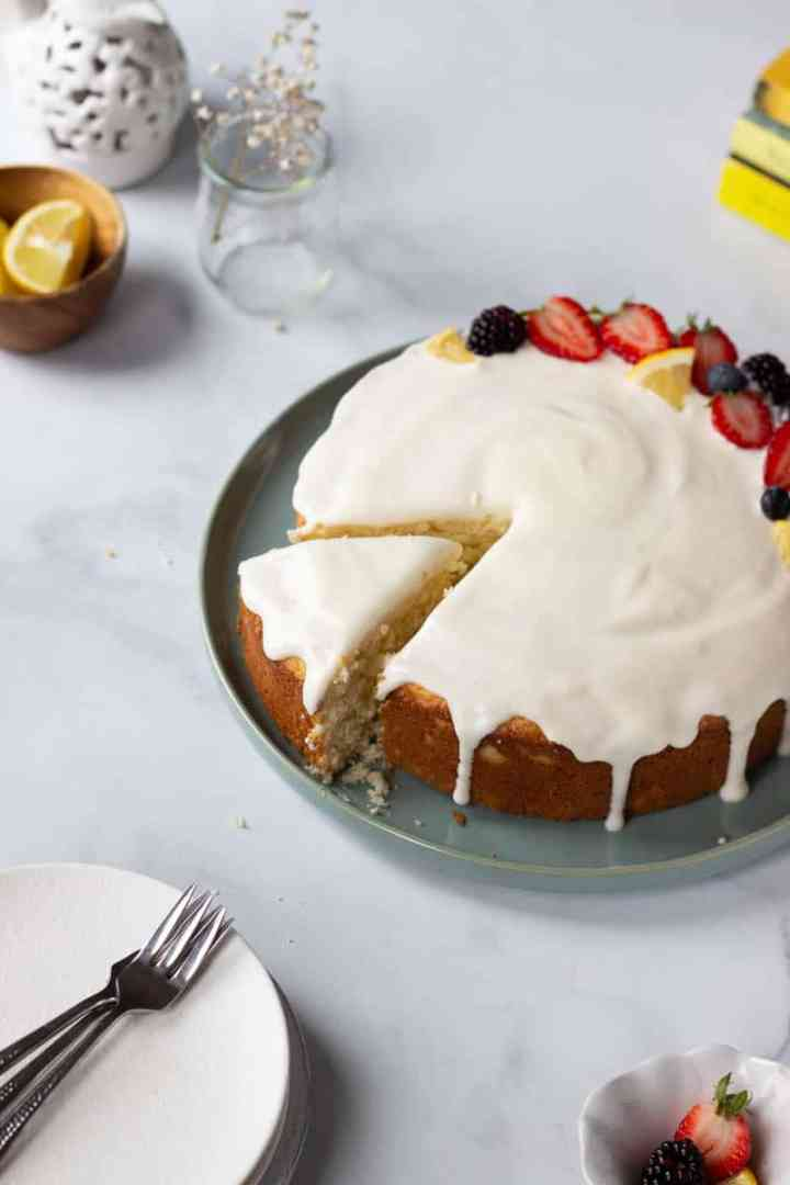 A lemon cake with cream cheese flaze with a slice partially pulled out. Plates, a little fruit and other yellow and white accents in the background