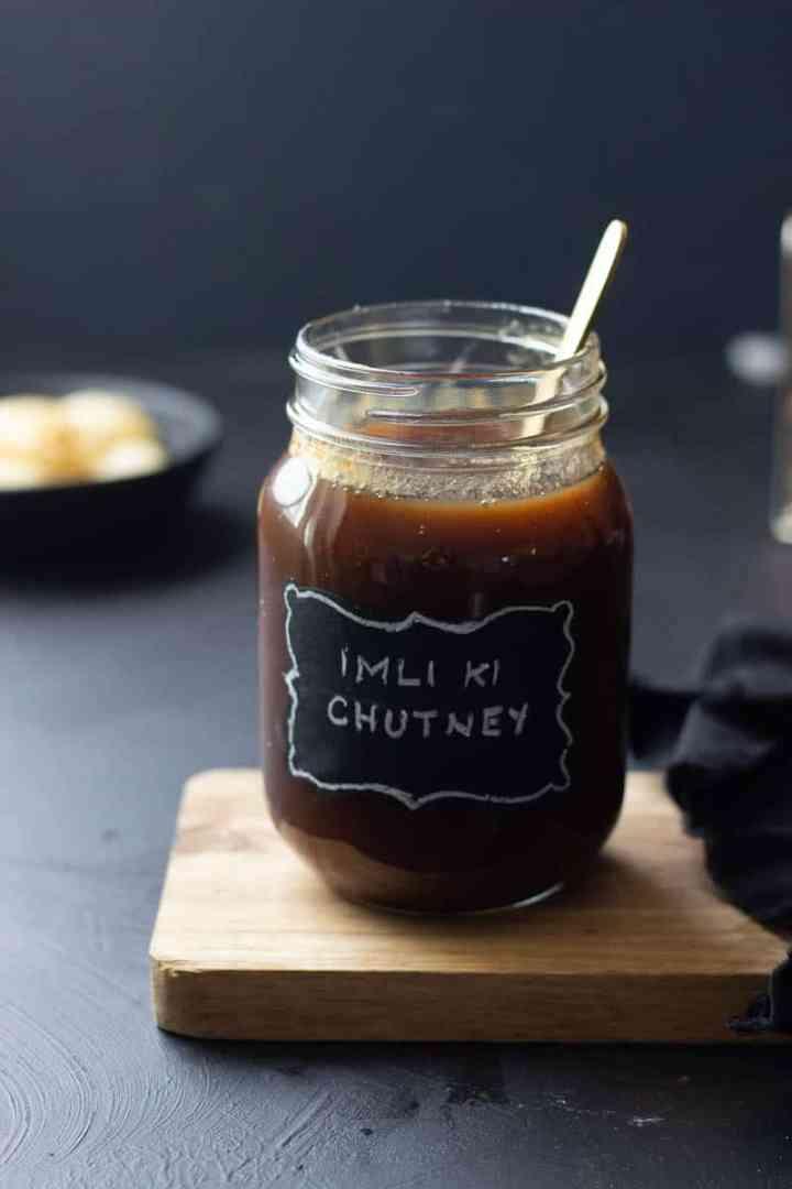 Imli ki Chutney in a jar, blurred pani puri in the background