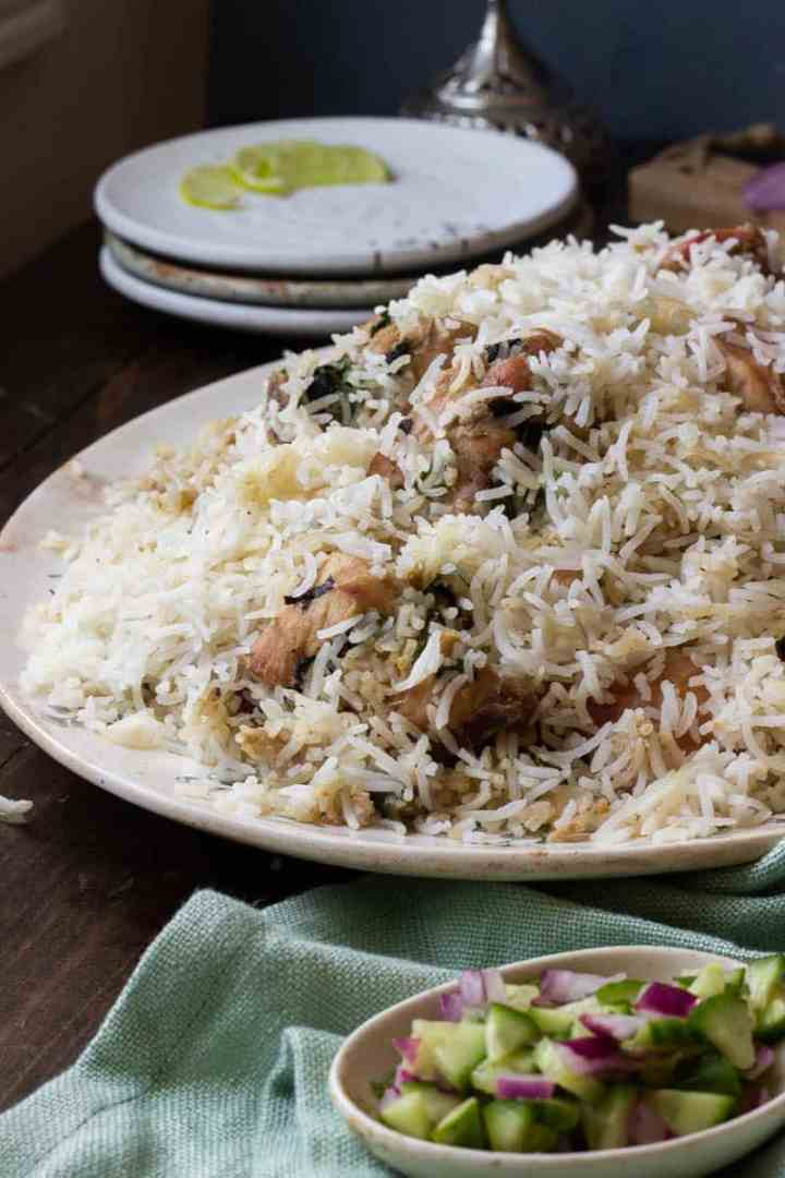 A dish of white biryani in ¾ view. A small dish of cucumbers and onions in the foreground